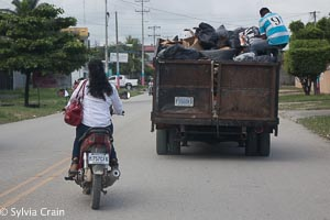 On the road - A very smartly dressed young woman on her scooter passing a garbage truck.  Note the red handbag on her shoulder and wedge heals.  Scooters and small cycles are a major method of transport throughout the country.